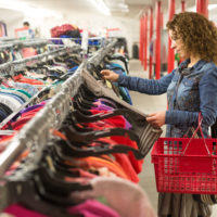 Female browsing through clothing In a Thrift Store